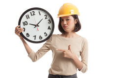 Asian engineer woman in bad mood with a clock Royalty Free Stock Photo