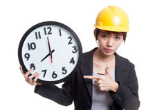 Asian engineer woman in bad mood with a clock. Stock Photo