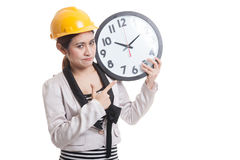 Asian engineer woman in bad mood with a clock. Stock Image