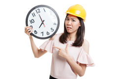 Asian engineer woman in bad mood with a clock. Royalty Free Stock Photos