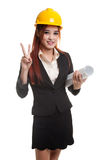 Asian engineer woman with blueprints show victory sign. Royalty Free Stock Photo