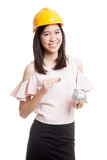 Asian engineer woman with a coin and piggy coin bank. Royalty Free Stock Photo