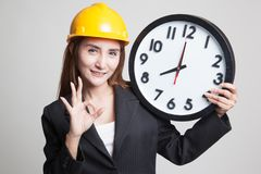 Asian engineer woman show OK with a clock. Stock Images