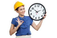 Asian engineer woman show OK with a clock Stock Photo