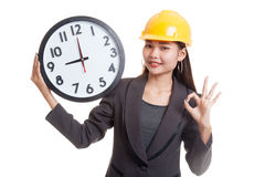 Asian engineer woman show OK with a clock. Royalty Free Stock Photography