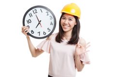 Asian engineer woman show OK with a clock. Royalty Free Stock Photos