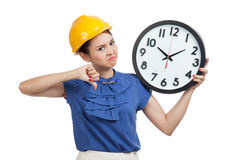 Asian engineer woman thumbs down with a clock Royalty Free Stock Photo