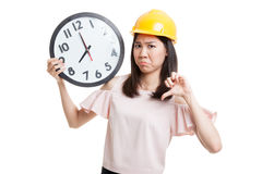 Asian engineer woman thumbs down with a clock. Royalty Free Stock Image