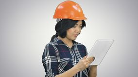 Asian engineer woman using tablet on white background. Close up. Professional shot in 4K resolution. 080. You can use it e.g. in your commercial video stock footage