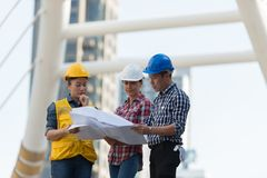 Asian engineers group consult construction on site building work. Ing while holding blueprint paper. in city background. teamwork concept Royalty Free Stock Photo