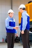 Asian engineers having agreement on construction site. Asian engineer having agreement handshake at construction machinery of construction site or mining company Stock Image