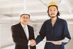 Asian engineers standing hand shake to successful in work royalty free stock photos