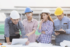 Asian engineers were consulted together and plan. In construction site stock images