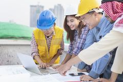 Asian engineers were consulted together and plan in construction site stock photos
