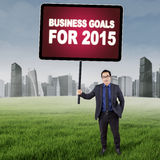 Asian entrepreneur with business goals. Young manager standing on the meadow while holding a board of business goals for 2015 Royalty Free Stock Image