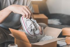 Asian entrepreneur teenager is carrying baby shoes and put in a cardboard box customer to deliver the product at home royalty free stock image