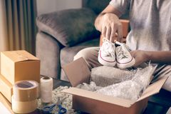Asian entrepreneur teenager is carrying baby shoes and put in a cardboard box customer to deliver the product at home stock photo