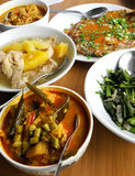 Asian ethnic food - assorted dishes. An assortment of local southeast asian cooking on brown wooden table.  Dishes include fish curry, chicken and papaya stew Royalty Free Stock Photo