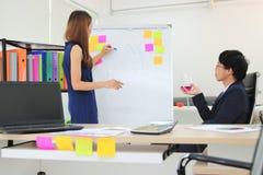 Asian executive boss listening employee explaining strategies on flip chart in boardroom.  stock photography