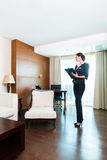 Asian executive housekeeper controlling hotel room. Asian Chinese Housekeeping manager or assistant controlling or checking the room or suit of a hotel with a Stock Photo