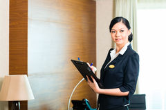 Asian executive housekeeper controlling hotel room. Asian Chinese Housekeeping manager or assistant controlling or checking the room or suit of a hotel with a Stock Image