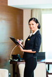 Asian executive housekeeper controlling hotel room. Asian Chinese Housekeeping manager or assistant controlling or checking the room or suit of a hotel with a Stock Images