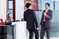 Manager and affiliate leaning at front desk of office royalty free stock images