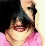 Asian expression. Lovely asian woman with her black shiny hair partly covering face. Eye and full red lips expressing playfulness royalty free stock photo