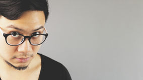 Asian eyeglasses man. A close-up of asian eyeglasses man with black t-shirt is looking at the camera stock image