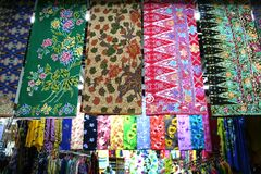 Asian fabrics. Traditional asian fabrics and clothes for sale in a shop in Malaysia Royalty Free Stock Photography