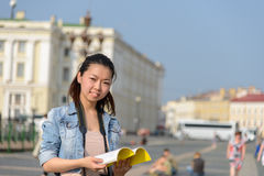 Asian famale tourist with guide book in city Royalty Free Stock Image