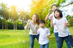 Lovely asian family. Asian family blowing bubbles in the park stock photography