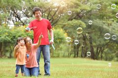 Asian family are blowing soap bubbles together. Happy young Asian family and their daughter are blowing soap bubbles together in nature at park outdoor. Family stock photography