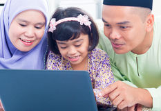 Asian family browsing internet. Southeast Asian family browsing internet at home. Muslim family living lifestyle Royalty Free Stock Image