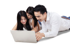 Asian family browsing internet with laptop. Portrait of Asian family lying down on the floor while browsing internet with laptop computer in the studio Royalty Free Stock Photography