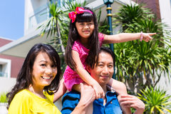 Asian family with child standing in front of home Stock Photos