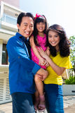 Asian family with child standing in front of home royalty free stock image