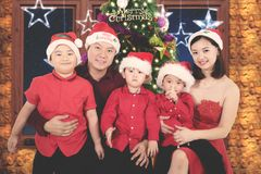 Asian family with Christmas tree background. Asian family smiling at the camera while sitting with Christmas tree background. Shot at home Stock Images