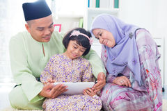 Asian family computer internet. Southeast Asian family using computer internet at home. Muslim family living lifestyle Stock Photo