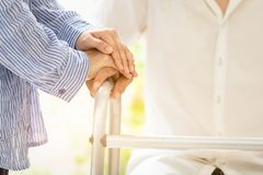 Asian family couple with walker during rehabilitation in home,young woman caregiver or wife hand holding hand of husband to stock photos