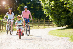 Asian Family On Cycle Ride In Countryside
