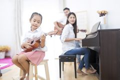 Asian family,daughter playing ukulele,father playing guitar,moth stock image
