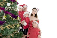 Asian family decorating a Christmas tree on studio. Asian family smiling at the camera while decorating a Christmas tree in the studio, isolated on white Royalty Free Stock Images