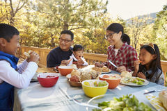 Asian family eating outside at a table on a deck in a forest Royalty Free Stock Image