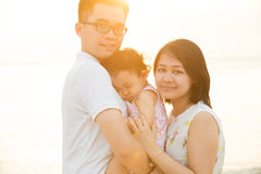 Asian family enjoying sunset beach Royalty Free Stock Photo