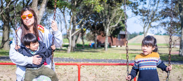 Asian Family enjoying a Swings in the park Royalty Free Stock Photography
