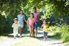Asian Family Enjoying Walk In Countryside. Happy Asian Family Enjoying Walk In Countryside With Children Running Stock Image