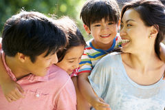 Asian Family Enjoying Walk In Summer Countryside. Hugging Each Other royalty free stock photo
