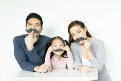 Asian family with fake mustache. Happy family playing in home. Family holidays and togetherness.  royalty free stock image
