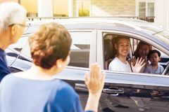 Asian family of father, mother and son waving goodbye to grandfather and grandmother as they take off their journey. Asian family of father, mother and son royalty free stock images